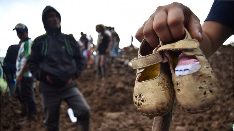 A person shows some children's shoes after a landslide, in the village Portachuelo, in the municipality of Rosas, Cauca, Colombia, 22 April 2019.
