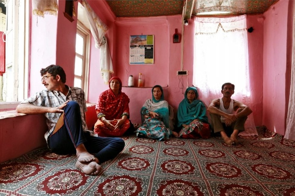 Members of a family watch television in their home in Srinagar as the city remains under curfew following weeks of violence in Kashmir, August 21, 2016.