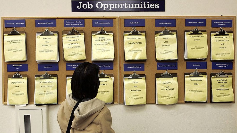 A job seeker looks at a job listing board at the East Bay Career Center February 2, 2006 in Oakland, California