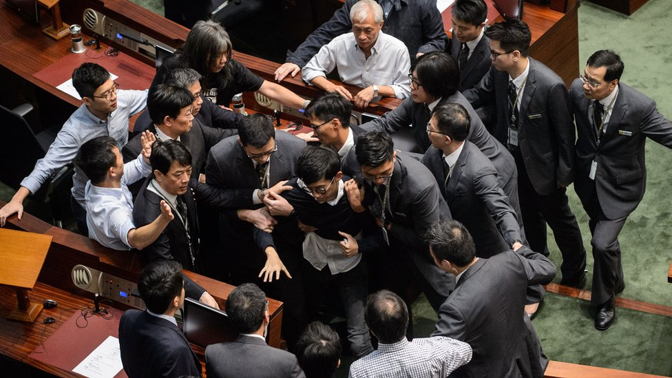 Newly elected lawmaker Sixtus Leung (C) is restrained by security after attempting to read out his Legislative Council oath at Legco in Hong Kong on November 2, 2016.