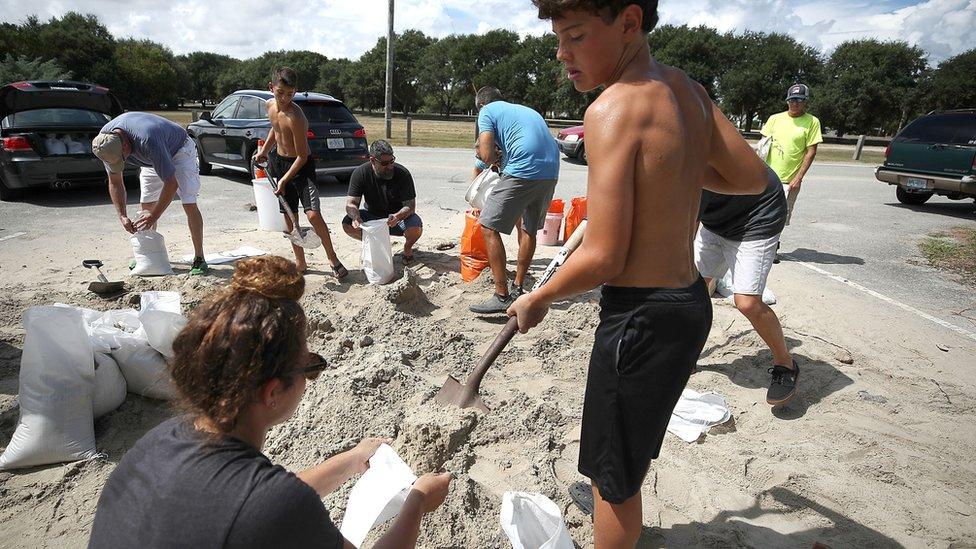 Joven llenando un saco de arena con ayuda de una mujer.