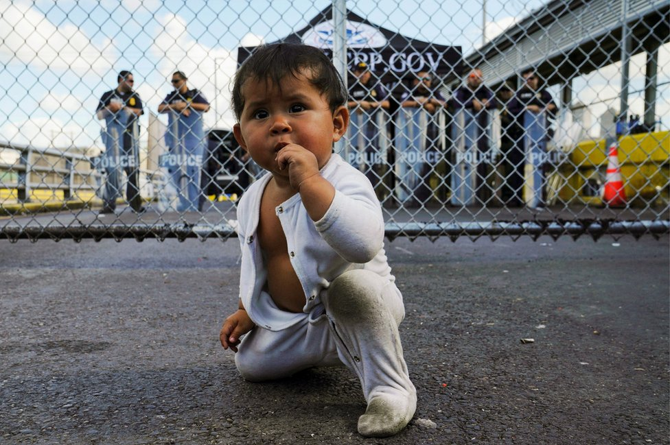 A baby in front of the gates to the Gateway International Bridge in Matamoros, Mexico