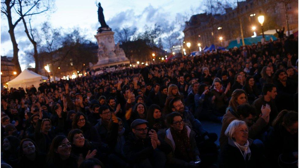 People listen to a speech during a gathering by the 'Nuit Debout' movement on Place de la Republique in Paris