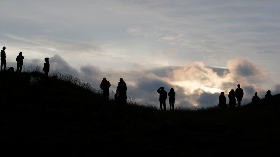 People look at the sunrise during the celebrations of the Summer Solstice, despite official events being cancelled amid the spread of coronavirus, in Avebury