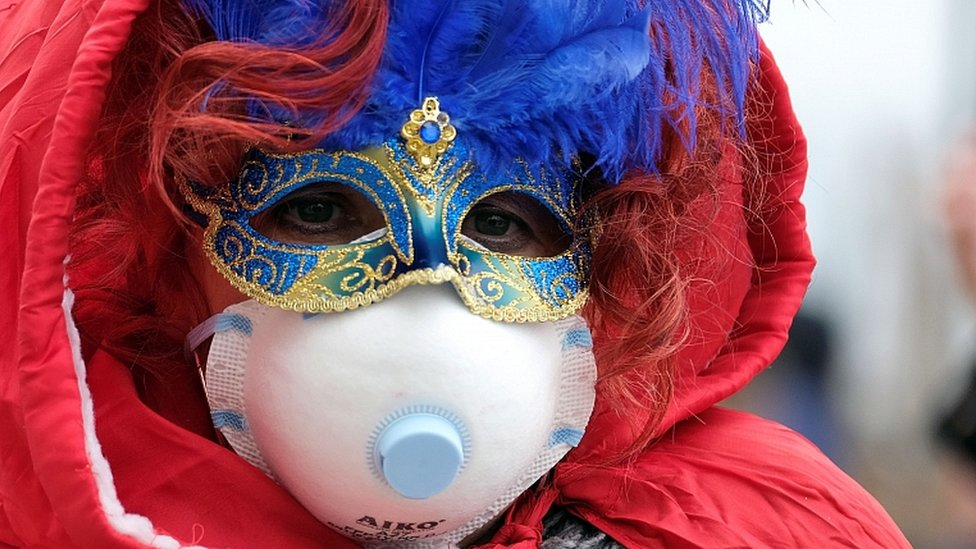 Masked carnival reveller wears protective face mask at Venice Carnival, 23 Feb 2020