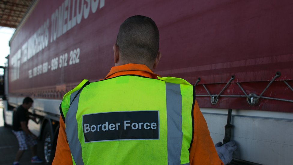 Man in high-vis jacket reading 'border force' inspects a lorry