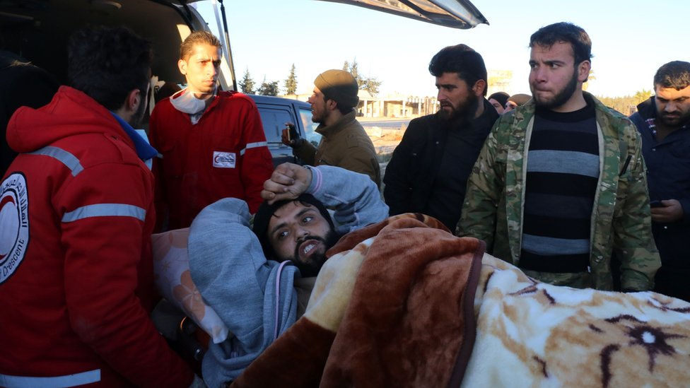 A wounded Syrian, who was evacuated from rebel-held neighbourhoods in the embattled city of Aleppo, is put into the back of an ambulance upon his arrival in the opposition-controlled Khan al-Assal region, west of the city