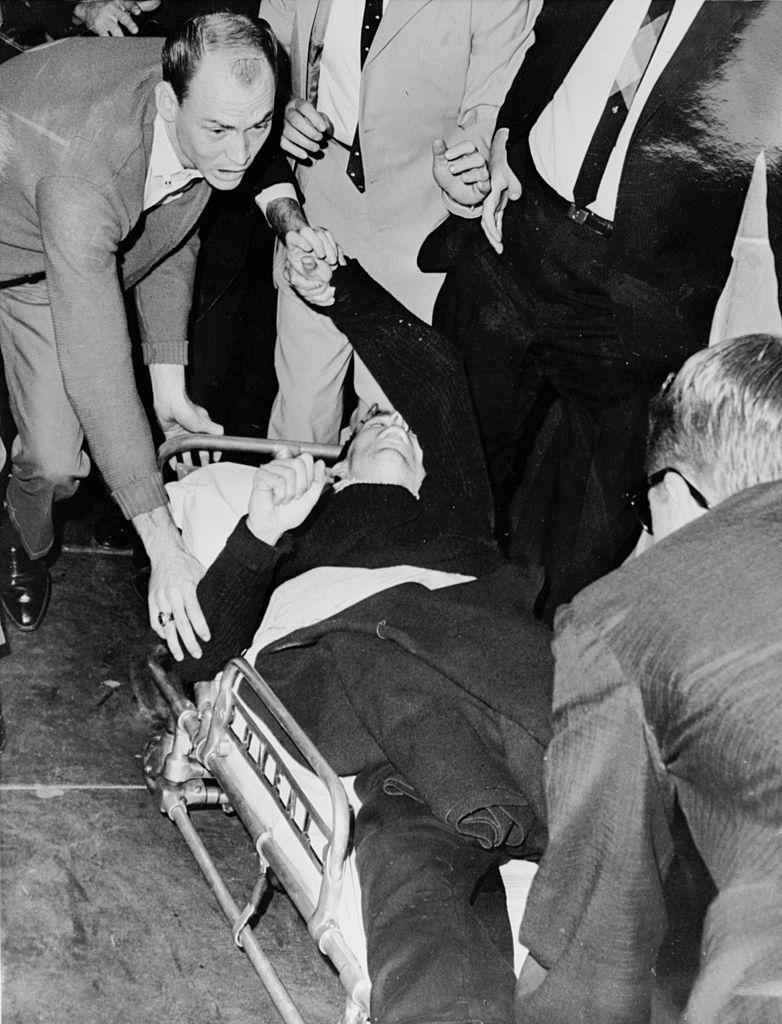 Oswald es llevado en camilla a una ambulancia tras ser baleado por Jack Ruby