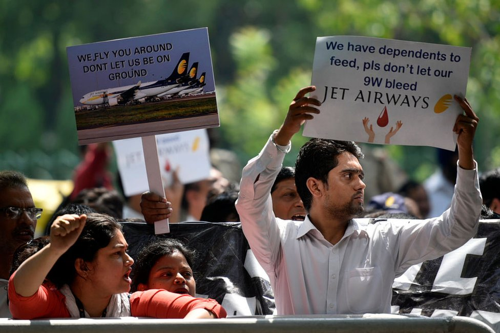 Jet Airways employees hold placards as they raise slogans during a protest against delayed salaries and the current shutdown crisis outside Rajiv Gandhi Bhawan at Jor Bagh on May 21, 2019 in New Delhi, India.