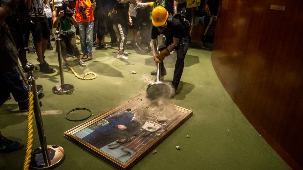 Protesters are seen smashing a portrait of Legislative Council Andrew Leung in Hong Kong