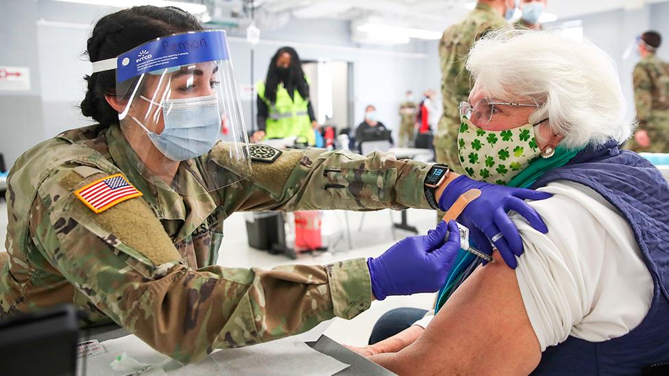 طبيبة في الجيش الأمريكي تعطي لقاحاً ضد فيروس كورونا لامرأة مسنة في مركز التطعيم في إلينوي. 3 فبراير /شباط 2021