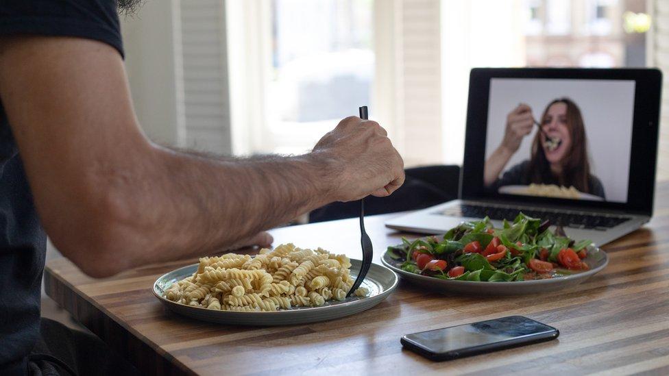 Un hombre y una mujer cenando a través de una videollamada.