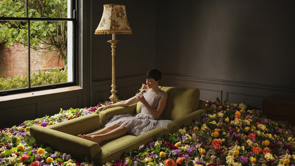 Mujer rodeada de flores