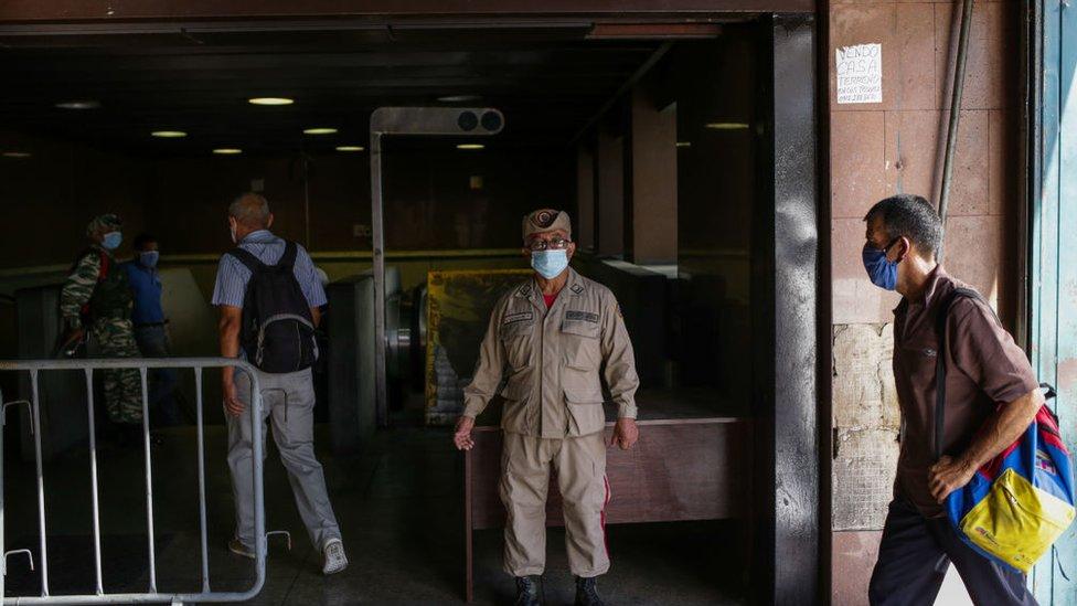 Un miembro de la policía venezolana en una estación del metro de Caracas asegurándose de que ningún pasajero ingrese sin mascarilla.