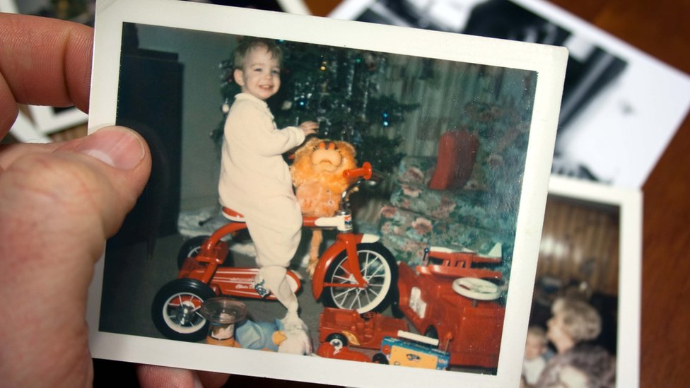 A vintage photograph of boy on tricycle at Christmas (stock photo)