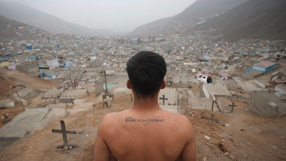 Sepulturero mira hacia un cementerio en las afueras de Lima, Perú.