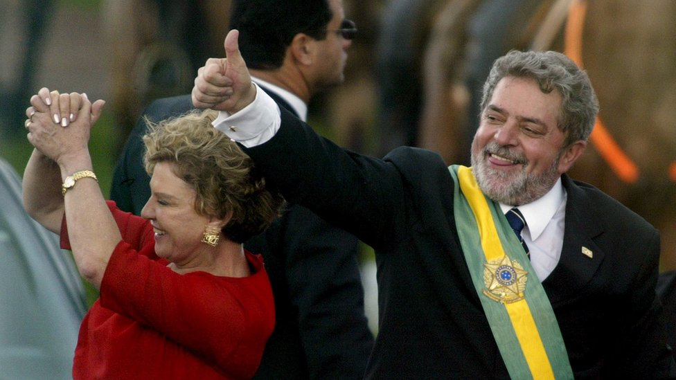 1 Jan 2003: Luiz Inacio Lula da Silva gestures to supporters as he rides past them with his wife, Marisa, after he received the presidential sash