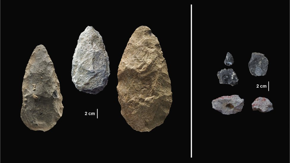 Three pear shaped hand axes. Three small obsidian points, black in colour. Two small, irregular blocks of pigment.
