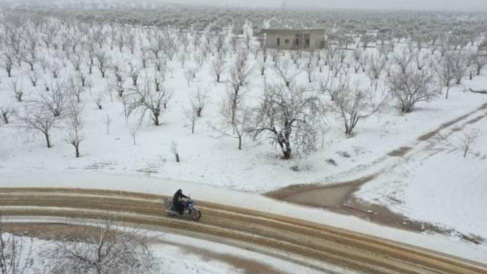 رجل يستقل دراجة بخارية على طريق وسط مزارع غطتها الثلوج