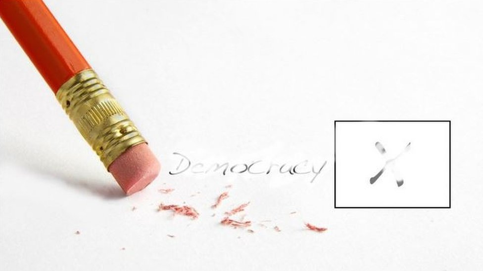 "Picture of pencil written word ""democracy"" being erased"