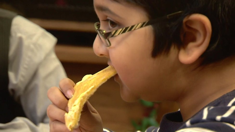 A child eating a slice of toast