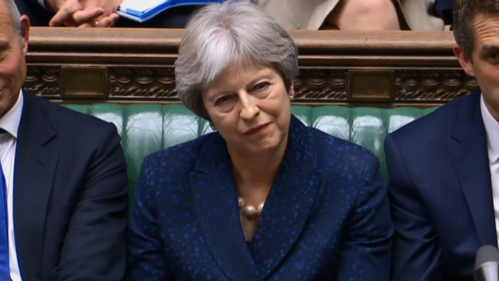Britain's Prime Minister Theresa May (C) listens in the Commons