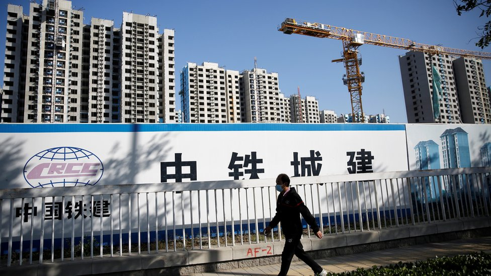 A man wearing a mask walks past a construction site of a residential compound in Beijing, China October 19, 2020.