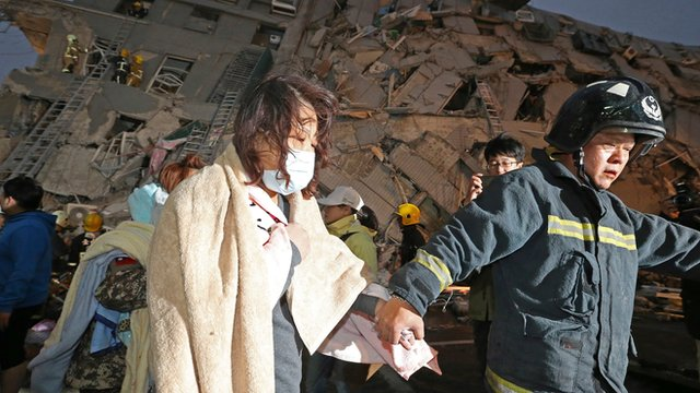A woman is led by a rescue worker from the site of a toppled building after an earthquake in Tainan, Taiwan