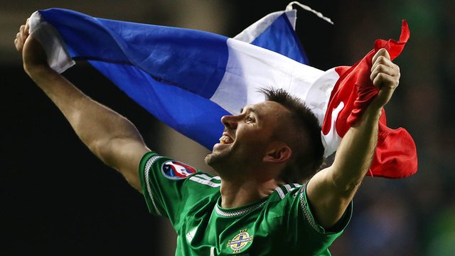 Gareth McAuley celebrates Northern Ireland's Euro 2016 qualification with the flag of finals hosts France