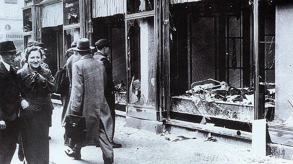 Transeúntes miran las vitrinas destrozadas de las tiendas de judíos en Berlín, tras los ataques de la Noche de los Cristales Rotos (Kristallnacht), noviembre de 1938