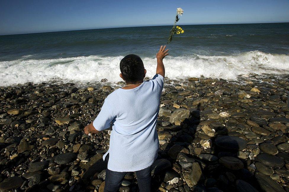 Una mujer lanza flores al mar el 16 de diciembre de 2009 para conmemorar el décimo aniversario del deslave de Vargas, ocurrido en Venezuela 1999.