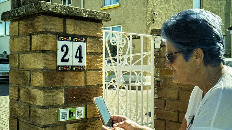 Rhyl house with woman scanning QR code of HistoryPoints.org plaque