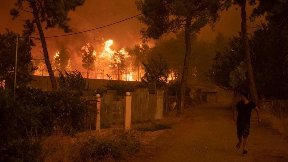 Un hombre se aleja de un incendio en la isla griega de Evia.