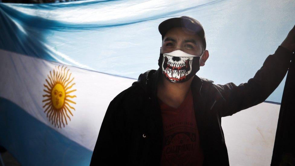 El hombre usa una máscara con un diseño de cráneo sangrante, con la bandera argentina en el fondo