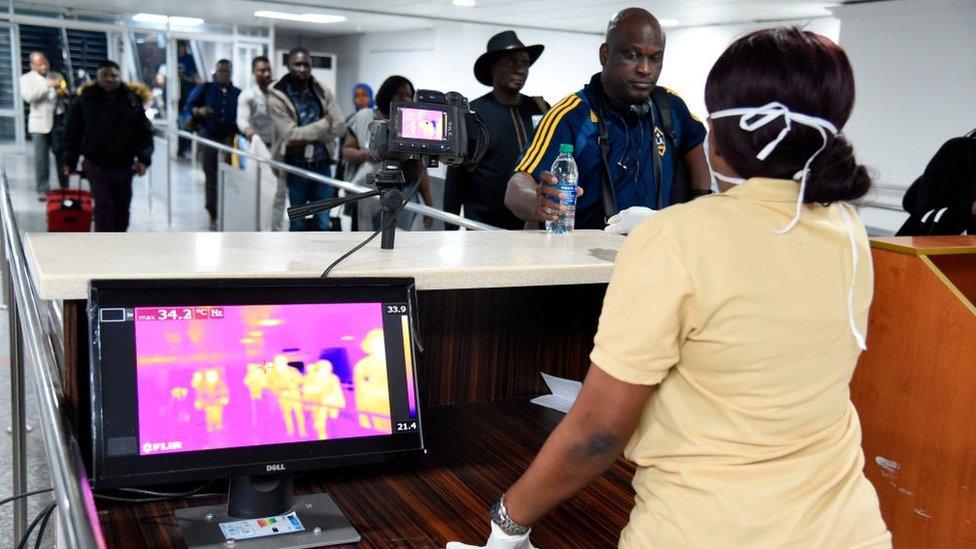 Un miembro del personal del Servicio de Salud Portuaria junto a un escáner térmico en el aeropuerto de Lagos, Nigeria.