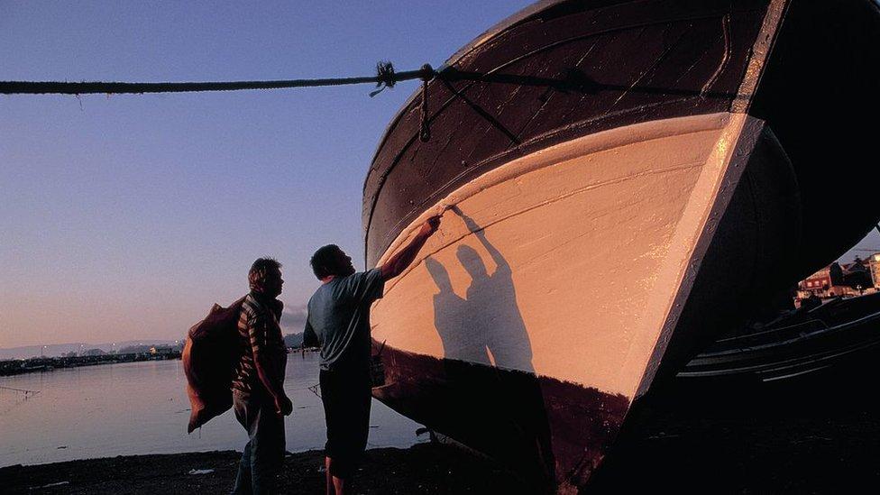 Dos hombres pintan un barco en Cambados.