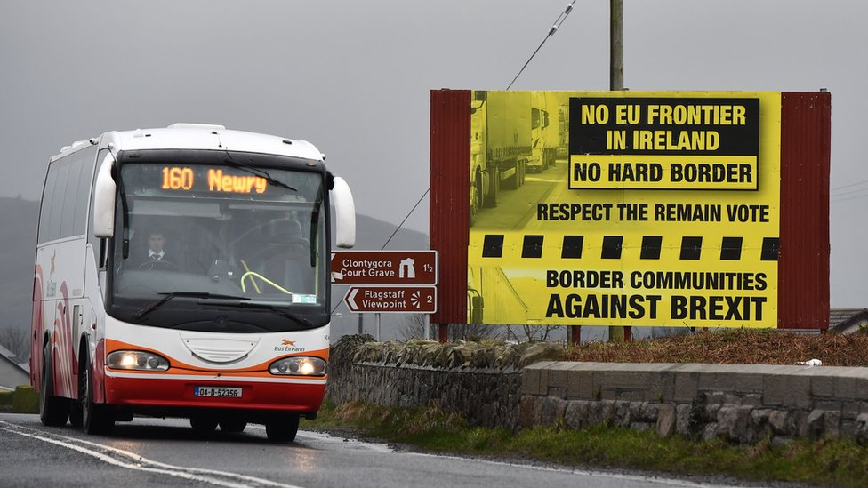 A coach passes a campaign sign rejecting a hard border in Ireland
