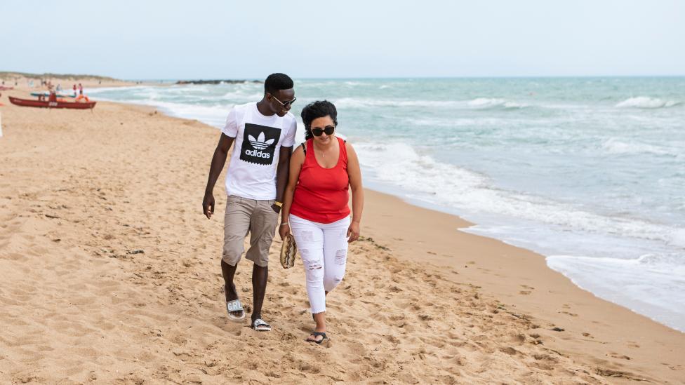 Muhammed Sanneh and Giusella Ferraro walking on a beach in Sicily