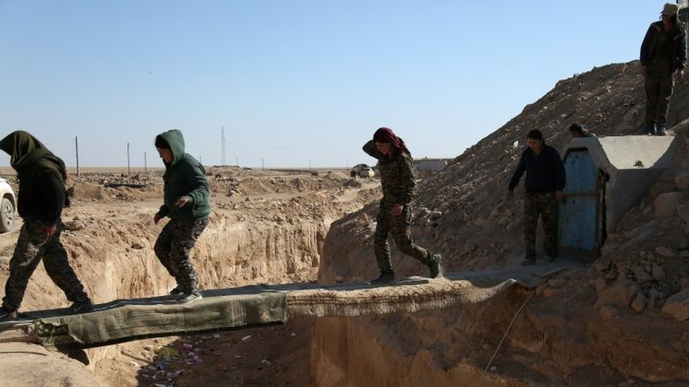 Syrian Democratic Forces (SDF) fighters cross a makeshift bridge in northern Deir al-Zor province, Syria on 21 February 2017.