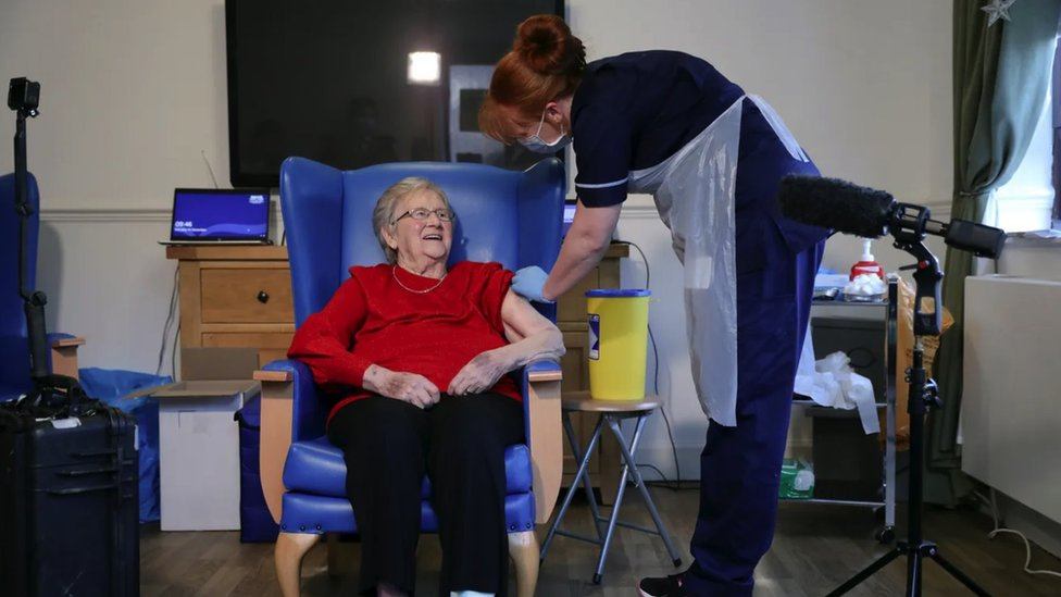 A nurse vaccinating an elderly patient