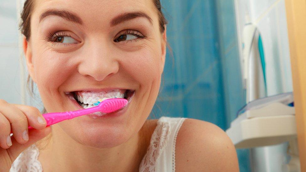 Mujer se cepilla los dientes.