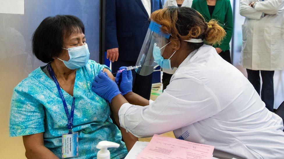 Uma profissional de saúde administra a segunda dose da vacina contra o coronavírus da Pfizer-BioNTech para a profissional Anita Quidangen, que é a primeira pessoa em Ontário a receber ambas as doses, 4 de janeiro , 2021