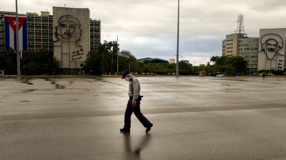 Un hombre con mascarillas camina por una calle vacía de La Habana.