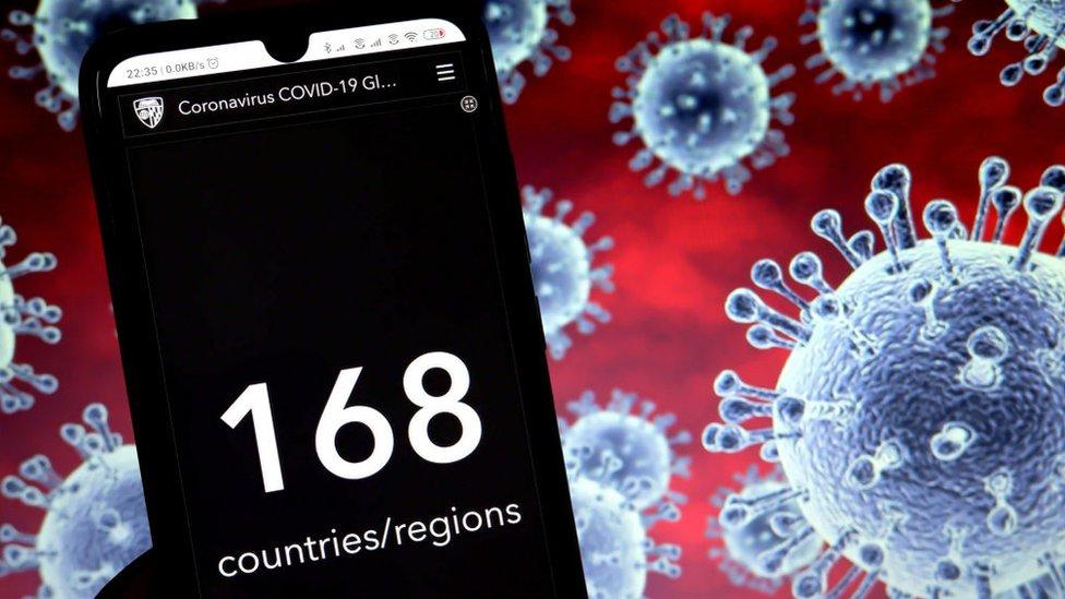 Un teléfono delante de una ilustración del coronavirus.