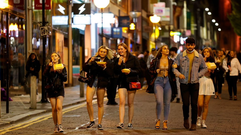 People walk outside bars in Liverpool before the new restrictions came into force