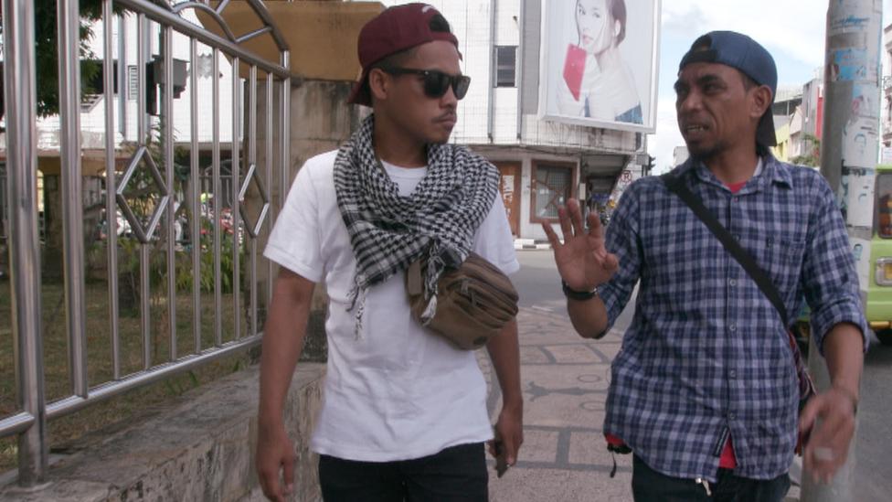 Ronald and Iskandar walk down the street, talking together