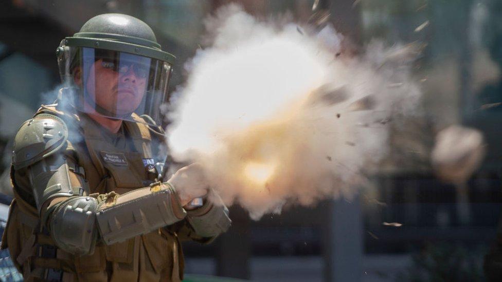 policía con casco lanza gas lacrimógeno