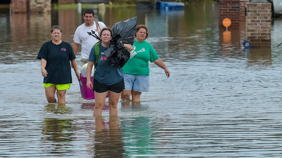 Four people wading through water that is almost up to their knees, carrying binbags and household items