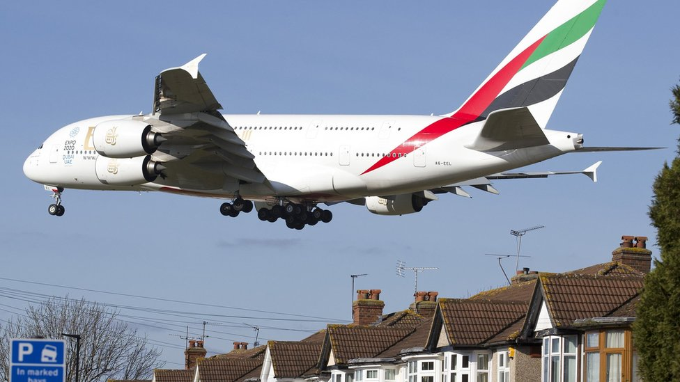 An Emirates Airbus A380 preparing to land at Heathrow Airport flies over houses in west London