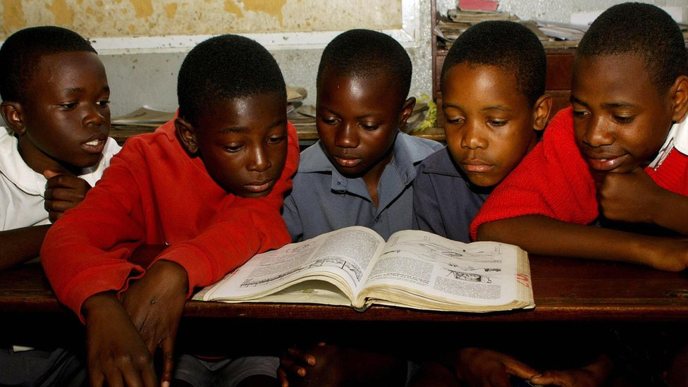 Zimbabwe pupils at a primary school in Zimbabwe's capital, Harare, read from the same textbook during a lesson on August 04, 2009